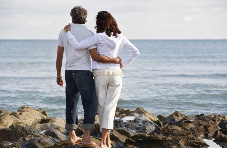 woman with dyspurenia overlooking ocean with husband